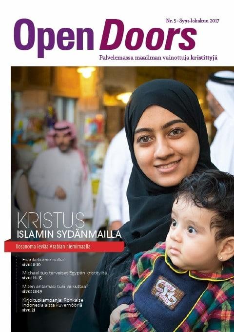 """Open Doors, vainottuja kristittyjä auttava maailmanlaajuinen järjestö, julkaisee suomessakin lehteä. Kuvassa vuoden 2017 syys-lokakuun lehden kansi, jossa Lähi-idästä kotoisin oleva hymyilevä nainen lapsensa kanssa. Lehden teema on: """"Kristus islamin sydänmailla""""."""