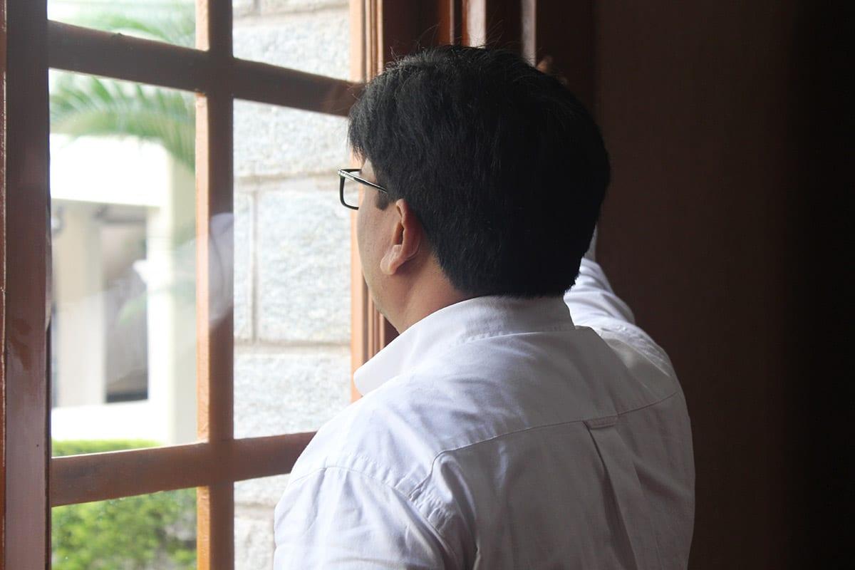 Intialainen mies katsoo ikkunasta ulos