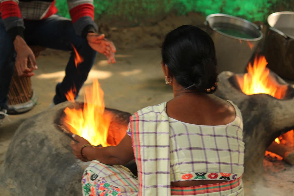 Intialainen nainen loimuavan nuotion edessä
