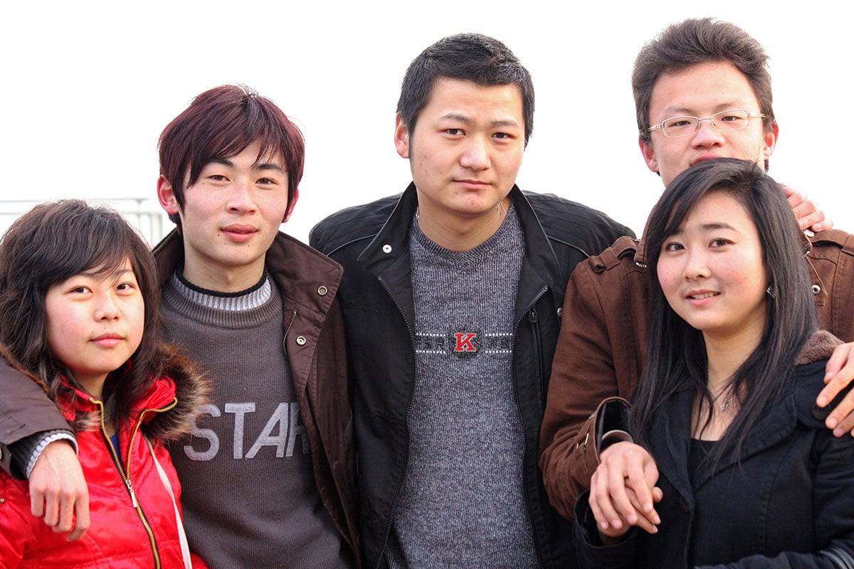 Kiinalainen perhe yhdessä katsoen kameraan