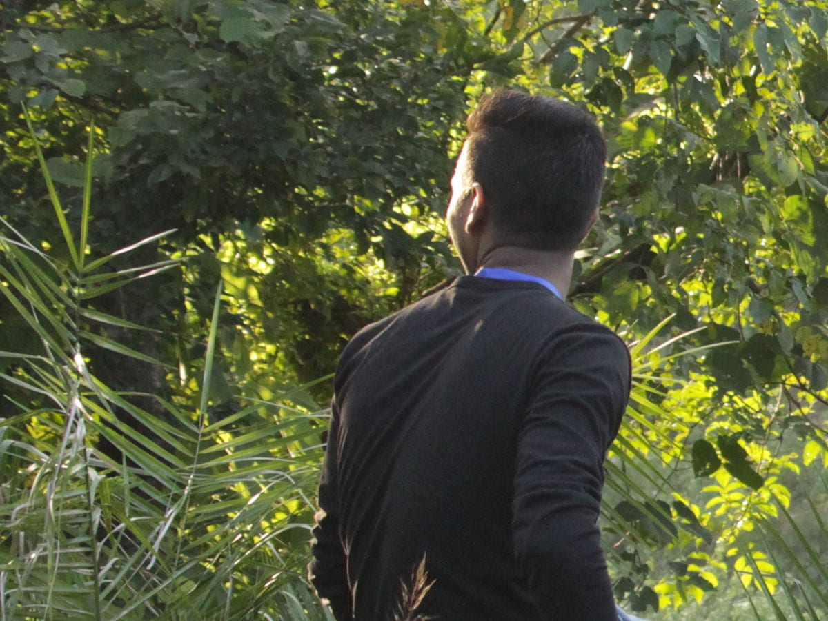 Vainottu Intialainen nuorimies istuu kasvillisuuden keskella kasvot käännettynä pois