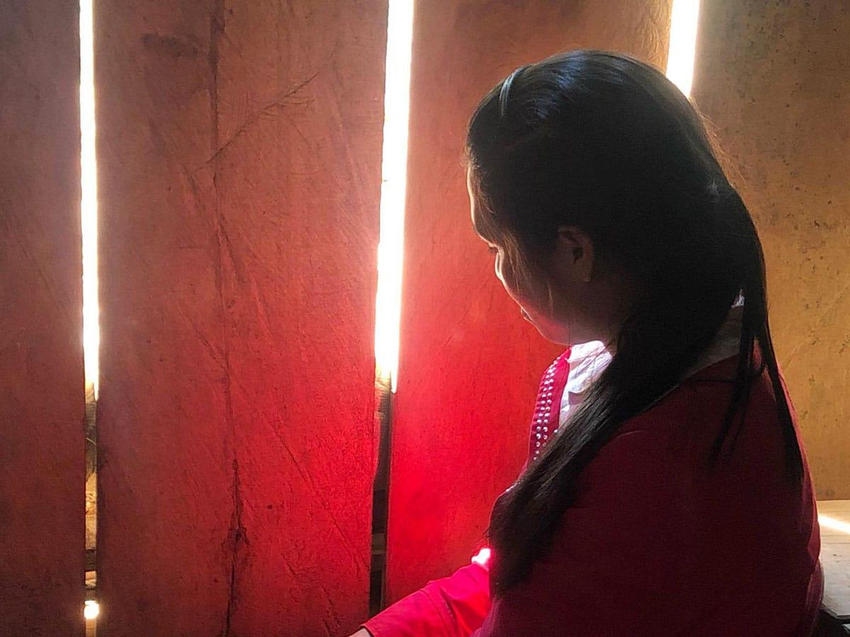 Vainottu Vietnamilainen Y Bi katsoo kotimajansa laudoituksen raosta ulos