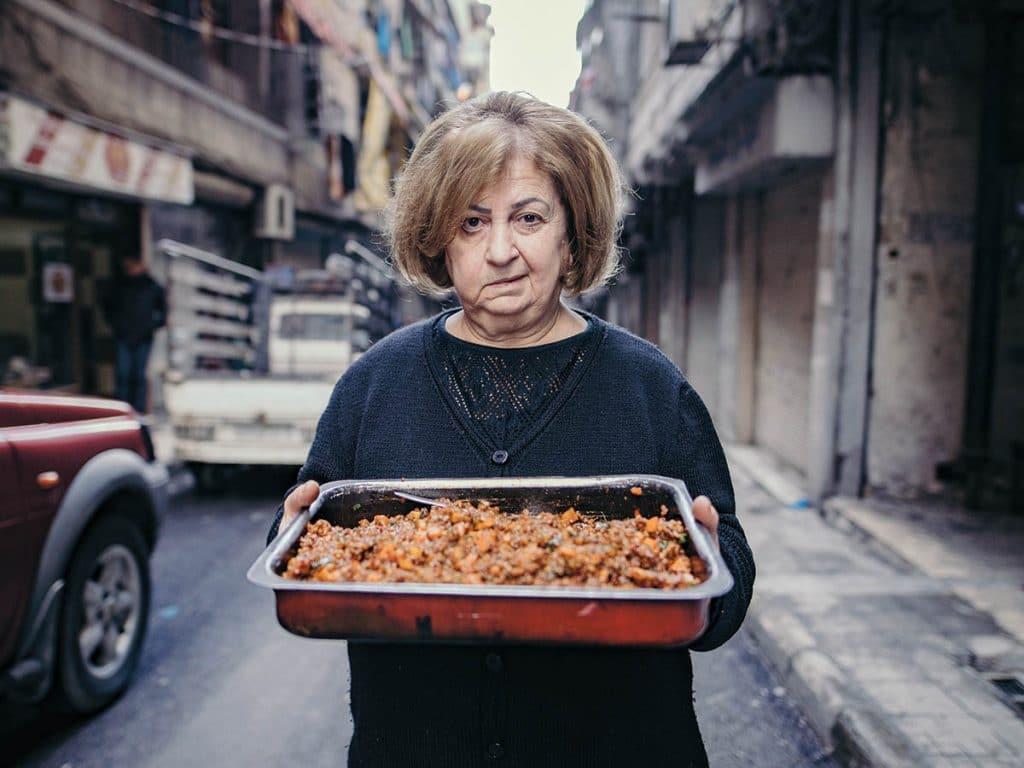 Syyrialainen nainen leipomukset edessään