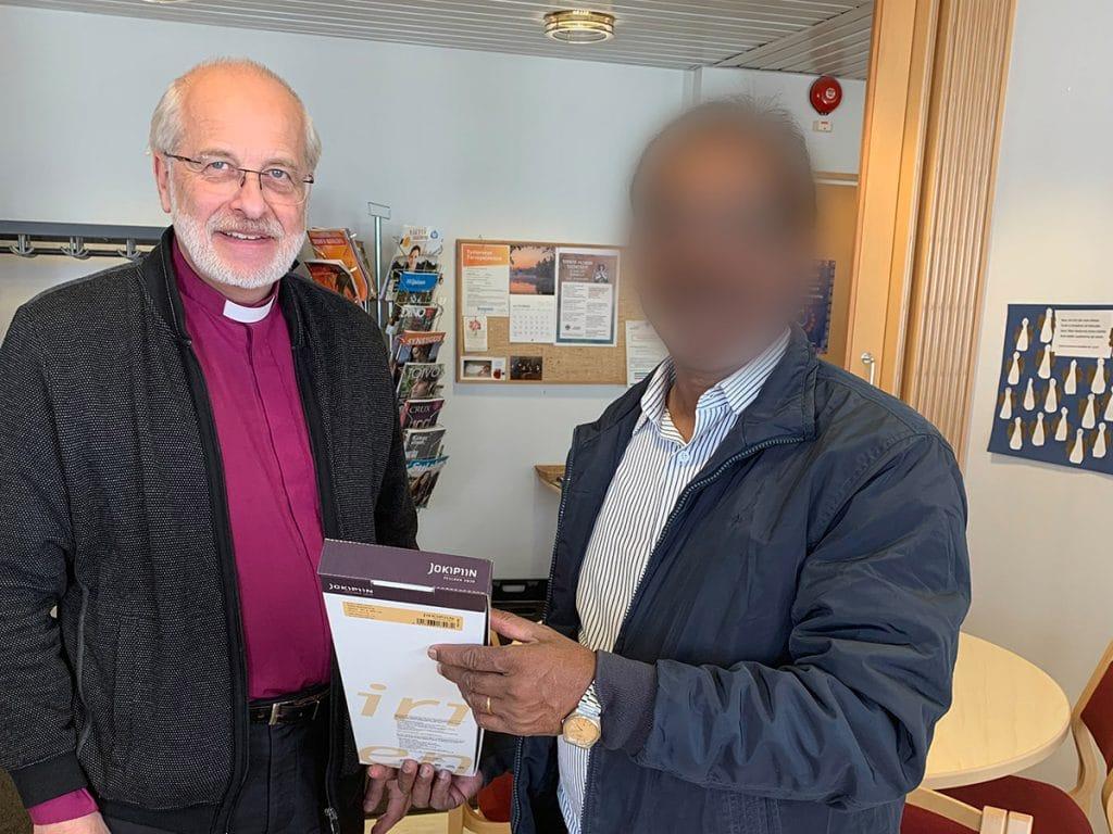 Pastori John ojentaa kirjeen Simo Peuralle
