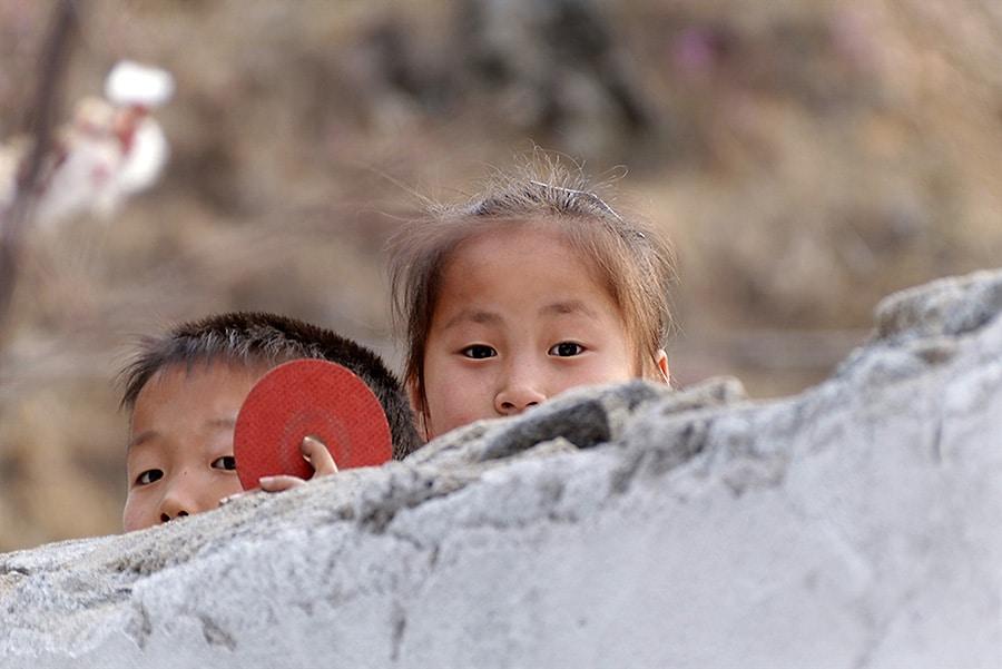Pohjois-Korea tytto ja poika kurkistavat kiven takaa