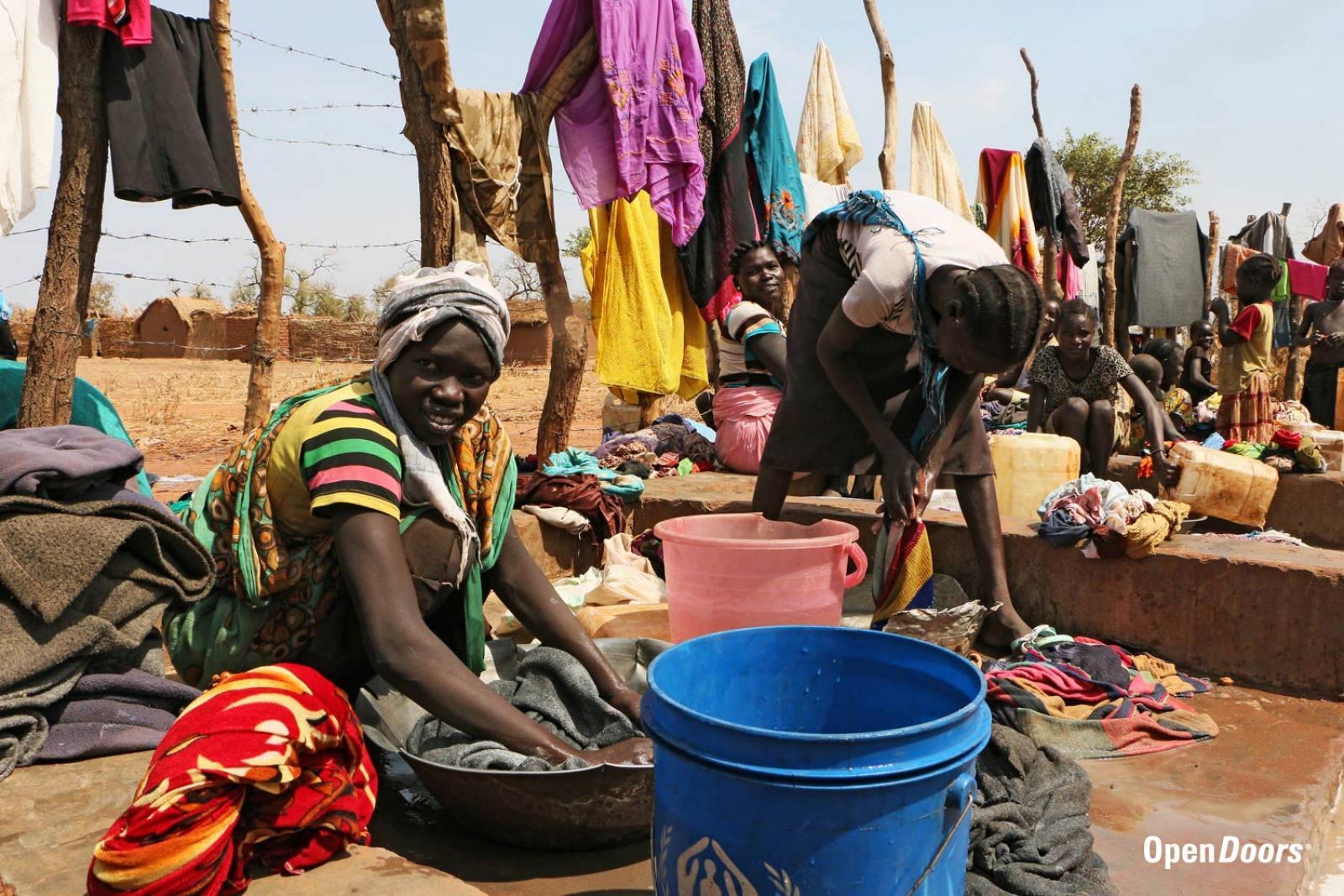 Nainen pesemässä vaatteita pakolaisleirillä