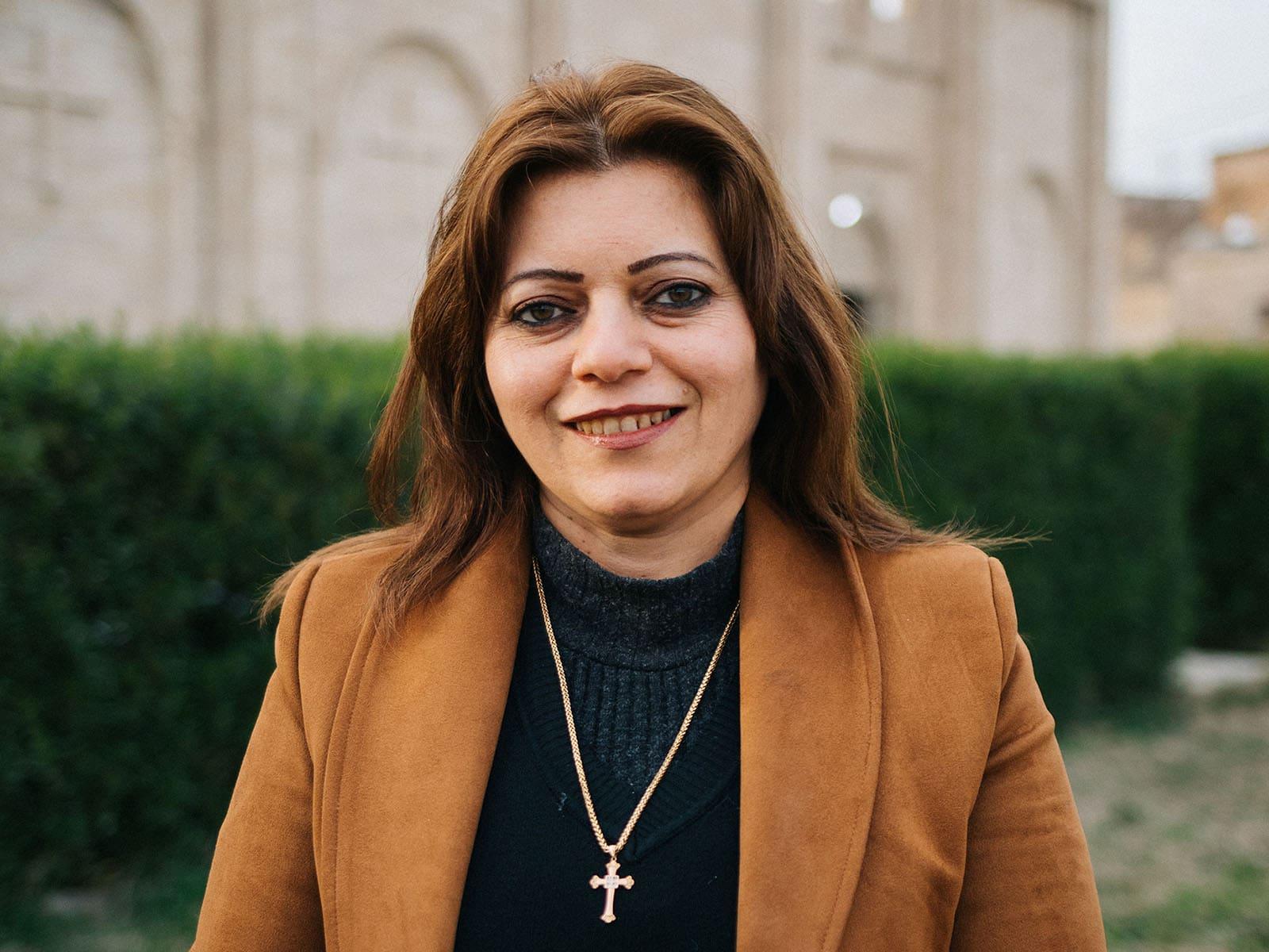 Irakilainen kristitty nainen pysyy kotimaassaan hymyilee kameralle