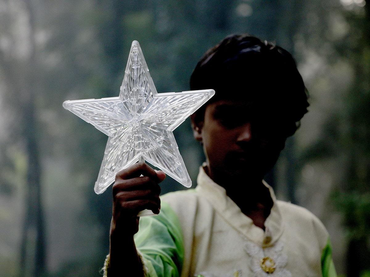 Bangladeshilainen kristitty tytto pitelee Joulun juhlistamiseksi tähteä