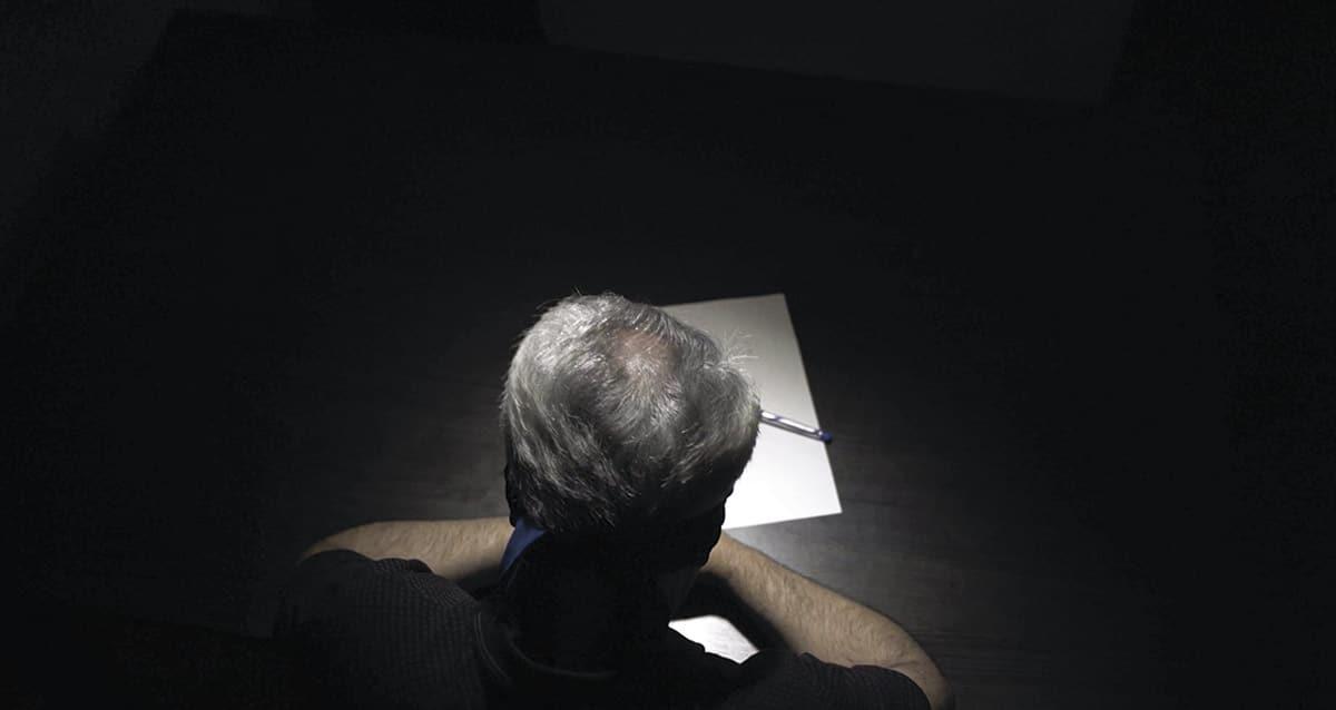 Mies pimeässä huoneessa kirjoituspöydän ääressä