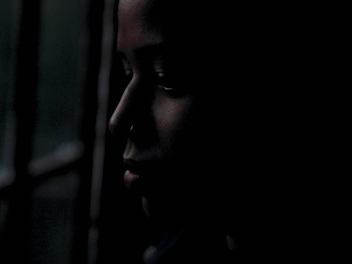Tyttö surullisena pimeässä huoneessa