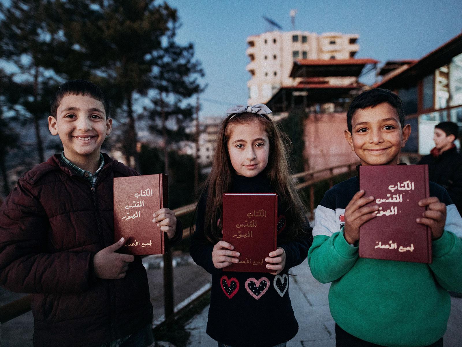 Syyialaisia lapsia Raamattujen kera